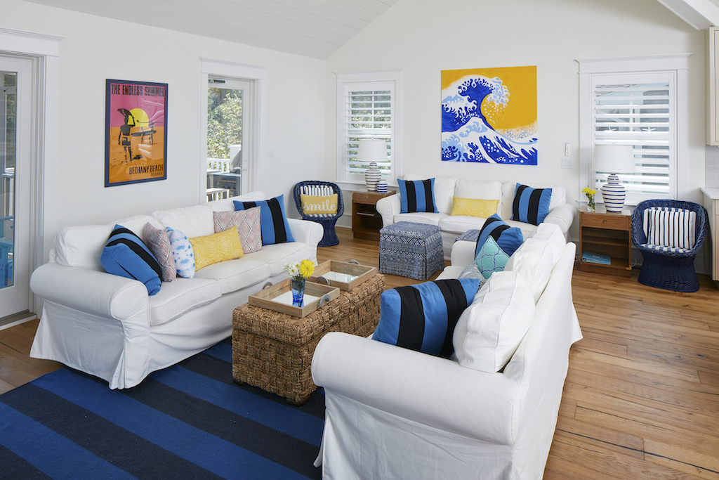 The Big Easy family room opposite view with bright yellow and blue wave painting